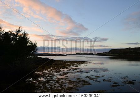 Loch dunvegan with trees silhouetted and pastel clouds.