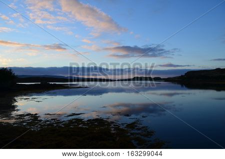 Pastel clouds reflected over Loch Dunvegan in Scotland.