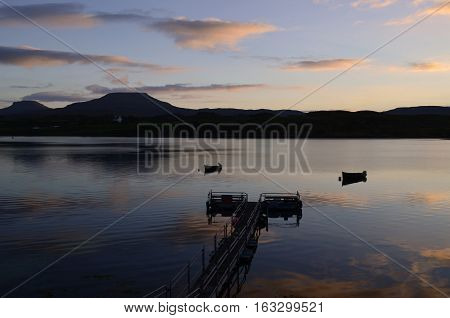 Gorgeous silhouetted pier and boats on Loch Dunvegan at Dawn.
