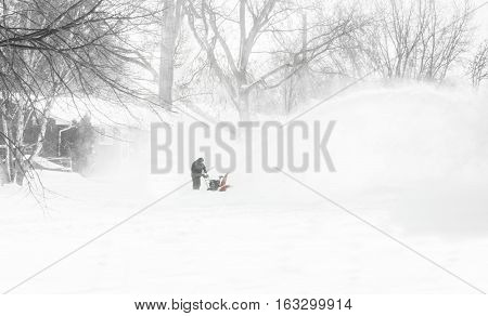horizontal image of a man in the distance blowing snow off his driveway with his snow blower after a snow storm.