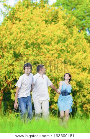Family Values Concepts and Ideas. Caucasian Family of Three Having Fun Together and Running in Summer Forest With Joined Hands. Vertical Image.
