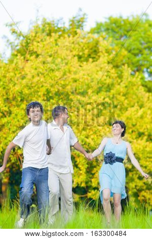 Family Values Concepts and Ideas. Caucasian Family of Three Having Fun Together and Running in Summer Forest With Joined Hands. Vertical Shot