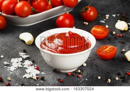 Tomato Sauce In White Bowl, Spice And Cherry Tomatoes On A Dark Background. Toning