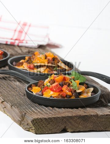 Colorful nachos served in individual cast iron fry pans.