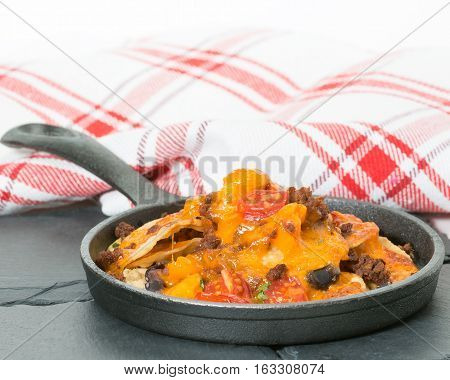 Delicious nachos served in a small cast iron fry pan.