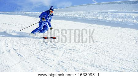 Young athlete skiing in Deux Alps french mountains on sunny day - Skier riding down for winter snow sport competition - Training and vacation concept - Soft focus on him - Warm vivid filter