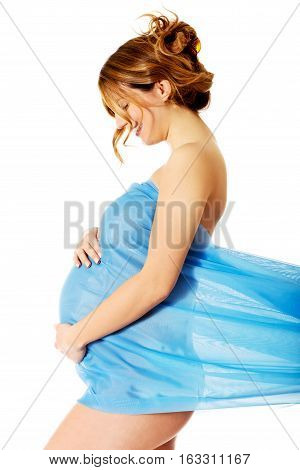 Beautiful pregnant woman wrapping at blue chiffon on white background.