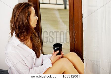 Woman drinking hot coffe at home. Looking throught window.
