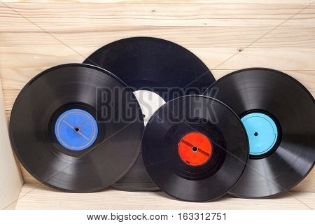 Vinyl record in front of a collection of albums vintage process. Copy space for text.