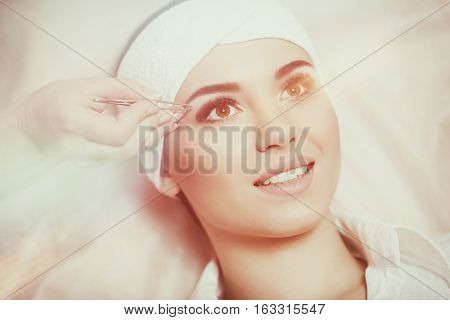 Beautiful young woman gets eyebrow correction procedure. Young woman tweezing her eyebrows in beauty saloon. Young woman plucking eyebrows with tweezers close up