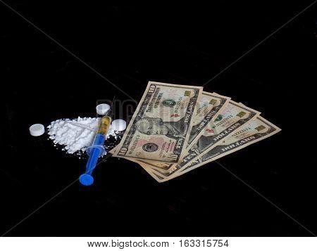 Injection syringe on cocaine drug powder, pills and dollar money bills on black background