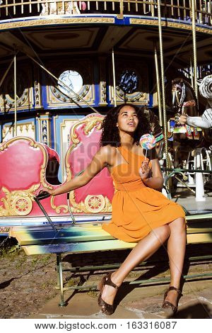 cool real african american teenage girl with candy near carousels at amusement park, lifestyle people concept close up