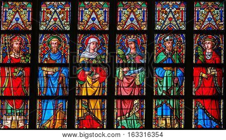 GHENT BELGIUM - DECEMBER 23 2016: Stained Glass window depicting Catholic Saints in the Cathedral of Saint Bavo in Ghent Flanders Belgium.