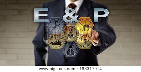 Torso of corporate manager activating E & P on an interactive screen. Oil and gas industry concept and petroleum market metaphor for the upstream industrial sector of exploration and production.