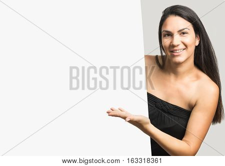 Beautiful young woman peeking out behind wall. Mockup