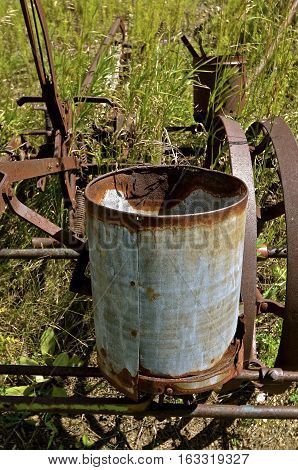 Rusty old seed canister mounted on a vintage corn planter