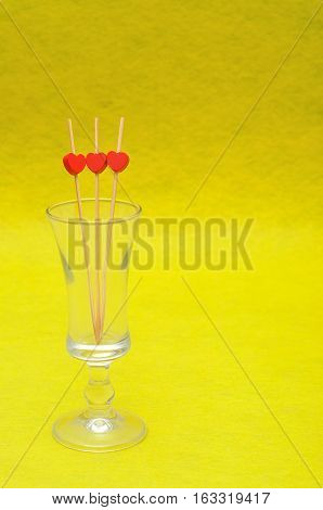 Valentine's Day. A shooter glass with three red hearts on sticks isolated against a yellow background