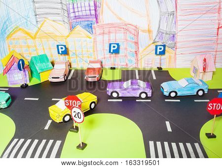 The traffic on a roads handmade paper maquette in driving school with crossings, parking, road signs and toy cars