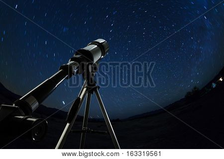 Telescope pointed to the clear night sky with many stars and constellations