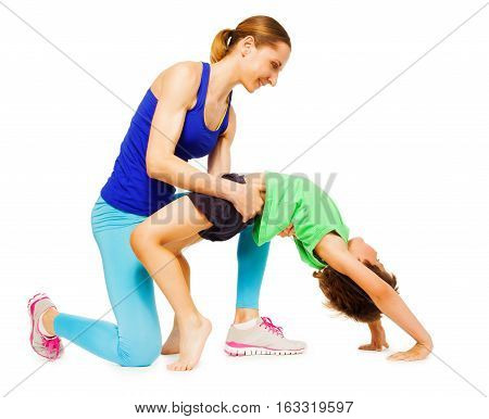 Young sporty mother helping her kid son making a crab position, isolated on white