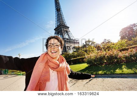 Portrait of happy young woman visiting autumn Paris, the Eiffel Tower on a background