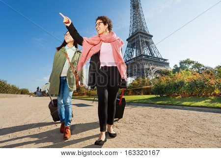 Two happy female tourists walking around Paris with their luggage and pointing to right direction