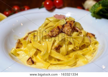 Chicken fettuccinne alfredo served on white plate