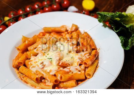 Rigatoni aerved with cheese souce on white plate