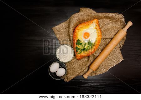 Khachapuri with eggs on sackcloth flour eggs and rolling pin on black table space for text