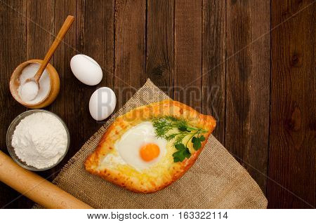 Khachapuri with eggs on sackcloth salt flour eggs and parsley on the wooden table space for text
