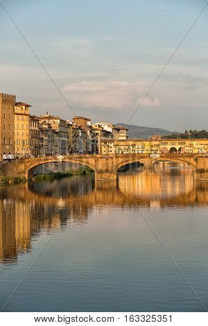 Florence, Italy-June 12, 2015.View of the Arno River and the buildings along it's banks, looking towards the Ponte Santa Trinita and Ponte Vecchio bridges in the late afternoon sunlight, Florence, Italy.