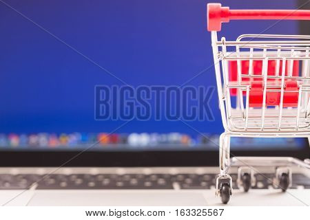 Rear view of a shopping cart on laptop. E-commerce concept.