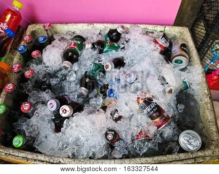 MAEKLONG, THAILAND-DECEMBER 11,2016 : drinks, many of which are immersed in a foam box being covered by ices for sale in the market.