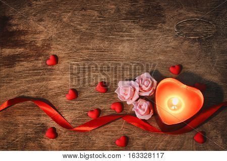 valentine's day dark background candle heart confetti pink roses scarlet ribbon on old wooden table retro style