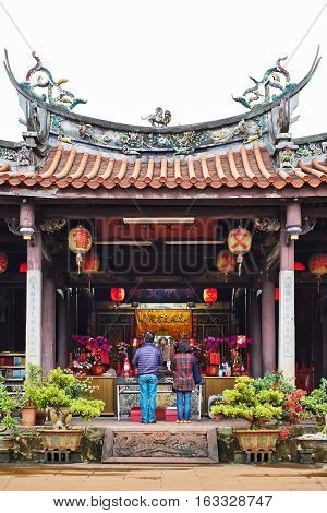 People pray for god in traditional oriental heritage temple in Taiwan (Chinese Translation on lantern : Jen-wen Academy on board : improve the society by education)
