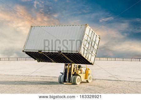Yellow industrial Forklift handling container box on blue sky background