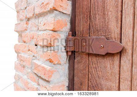 old brown door hinge against brick wall