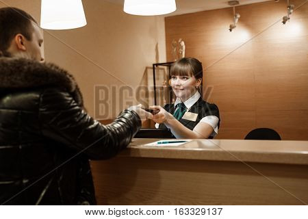 Pretty hotel female receptionist in uniform giving key to male guest