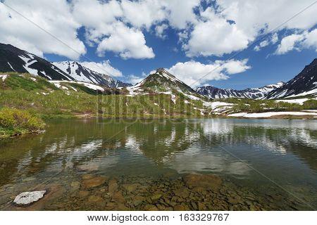 Beautiful summer landscape of Kamchatka Peninsula: view of Mountain Range Vachkazhets, mountain lake and clouds in blue sky on sunny day. Eurasia, Russian Far East, Kamchatka Region.