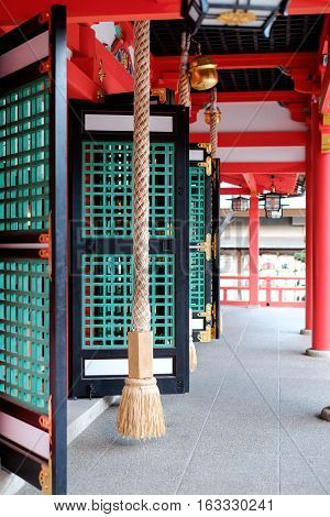 Rope door window red roof and bells in traditional japanese temple Kyoto Japan