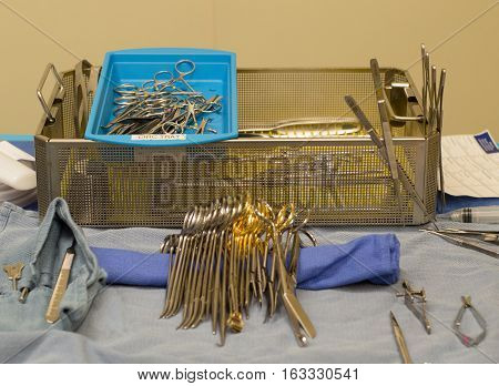 Sterile instruments in a metal pan and on a draped table being prepared for surgery. Photographed with a shallow depth of field.