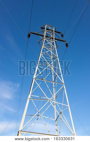 Tall Steel Transmission Tower Against Blue Sky