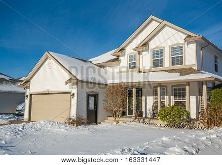 Family luxury house with front yard in snow. Residential house on winter sunny day