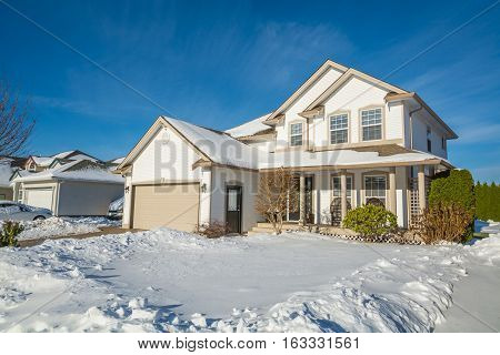 Single family luxury house with front yard in snow. Residential house on winter sunny day