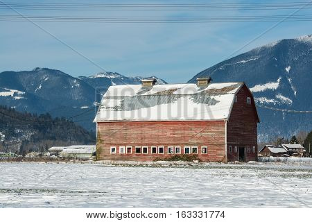 Industrial agriculture building in disrepair. Old red barn on mountain view background. Panoramic view on animal farm on winter sunny day on blue sky background