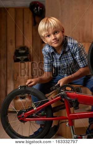 Portrait of preteen boy fixing gear of bicycle