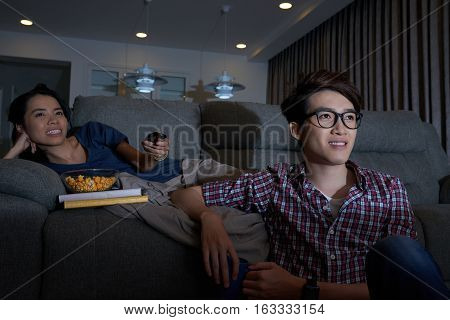 Young couple sittting at home and enjoying tv program
