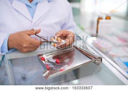 Pharmacist giving certain amount of pills to patient