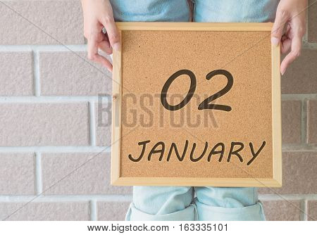 Closeup calendar at the cork board in hand of asian woman in front of her legs with 2 january word on brick wall textured background
