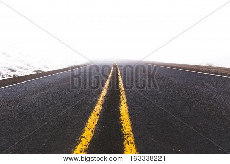Double yellow line on a highway or interstate road. Foggy winter setting.